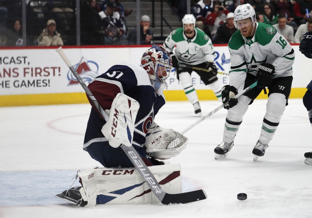 Colorado Avalanche goaltender Philipp Grubauer, front, stops a shot as Dallas Stars center Joe Pavelski drives to the crease in the second period of a...