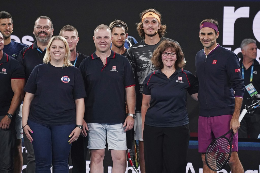 Roger Federer of Switzerland, second right, and Stefanos Tsitsipas of Greece, fourth right, pose with Deb Borg, third right, and fellow Australian fir...