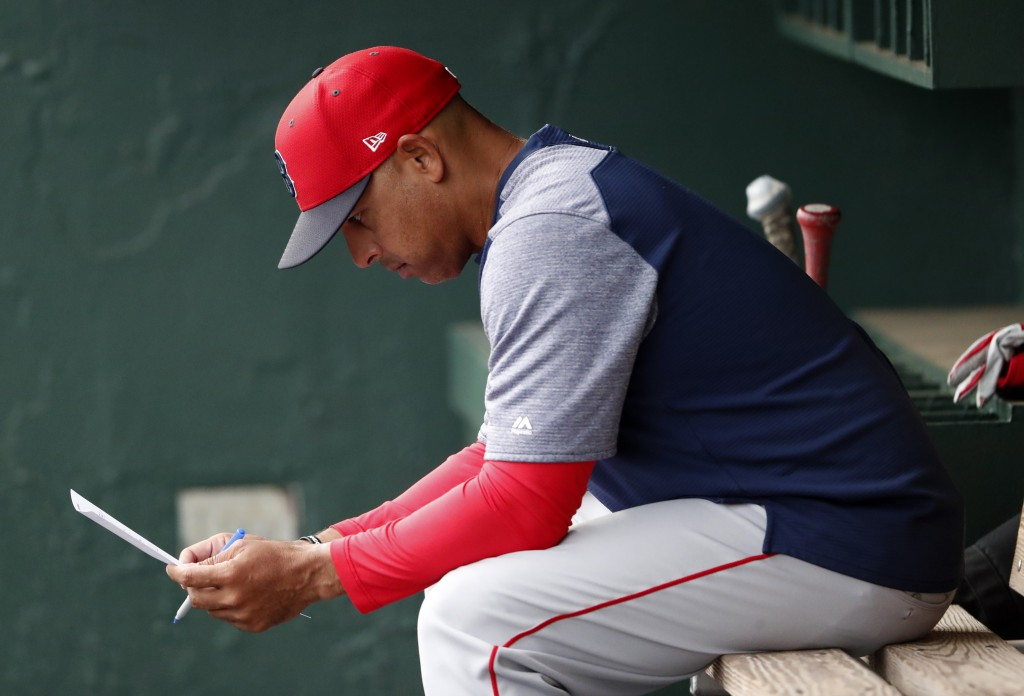 FILE - In this March 20, 2019, file photo, Boston Red Sox manager Alex Cora looks over the lineup before the team's spring training baseball game agai...