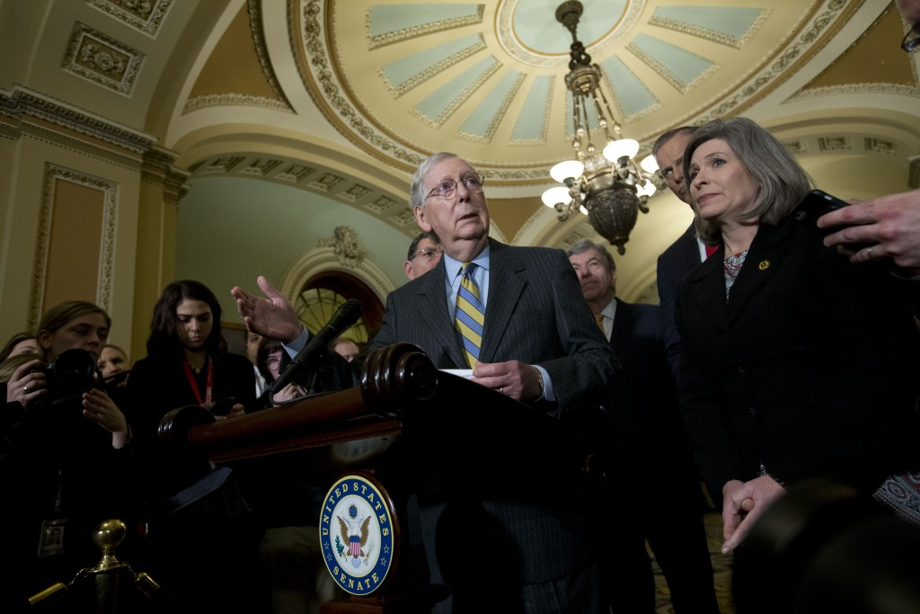 Senate Majority Leader Mitch McConnell, R-Ky., accompanied by Sen. Joni Ernst R-Iowa, and other senators, speaks outside of the Senate chamber, on Cap...