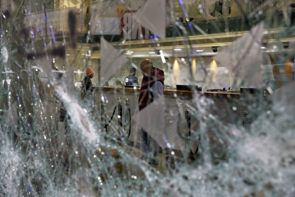 Bank employees are seen through the broken glass of Bank of Beirut that was smashed by anti-government protesters in Beirut, Lebanon, Wednesday, Jan. ...