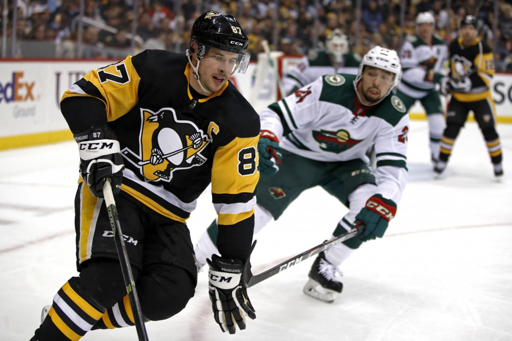 Pittsburgh Penguins' Sidney Crosby (87) works the puck in the corner with Minnesota Wild's Matt Dumba (24) defending during the second period of an NH...