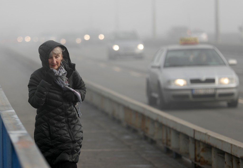A woman walks across a busy bridge in Belgrade, Serbia, Wednesday, Jan. 15, 2020. Serbia's government on Wednesday called an emergency meeting, as man...