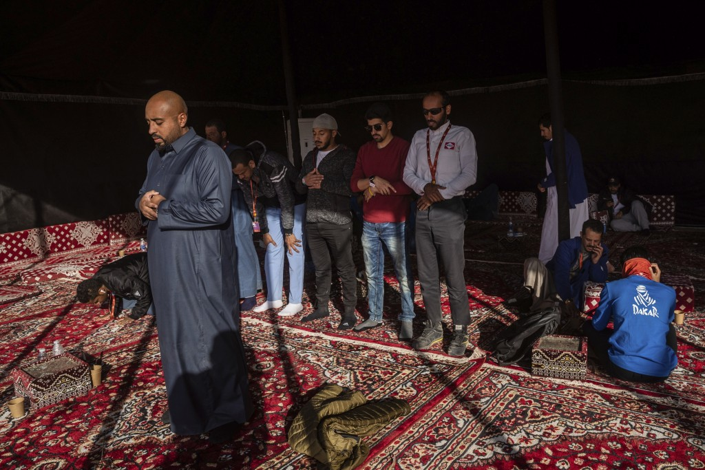 In this Monday, Jan. 13, 2020 photo, Muslims pray at a tent after stage eight of the Dakar Rally in Wadi Al Dawasir, Saudi Arabia. Formerly known as t...