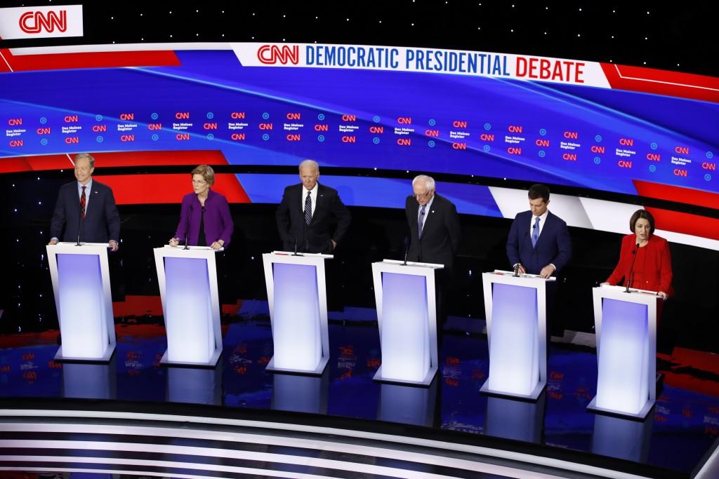 Sen. Amy Klobuchar, D-Minn., right speaks as from left, Democratic presidential candidates businessman Tom Steyer, Sen. Elizabeth Warren, D-Mass., for...