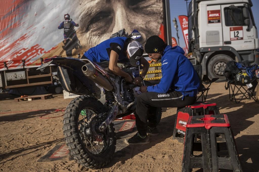 "In this Monday, Jan. 13, 2020 photo, Sara Garcia of Spain checks her Yamaha motorbike, next to his partner Javier Vega of Spain at the Dakar rally ""pa..."