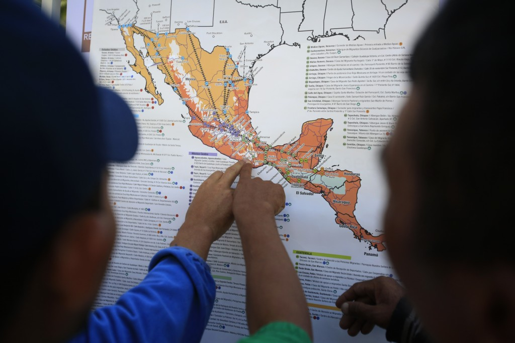 FILE - In this Nov. 9, 2018 file photo, migrants discuss their journey using a map posted inside the sports complex where thousands of migrants have b...