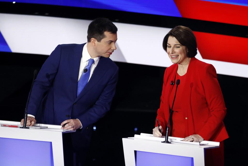 Democratic presidential candidates former South Bend Mayor Pete Buttigieg, left, and Sen. Amy Klobuchar, D-Minn., right, talk during a break Tuesday, ...