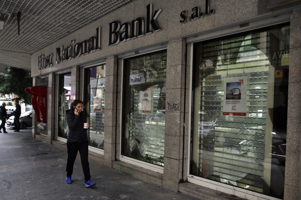 A woman passes by the broken facade of Beirut National Bank that was smashed by anti-government protesters in Beirut, Lebanon, Wednesday, Jan. 15, 202...