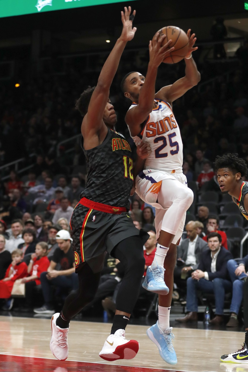 Phoenix Suns forward Mikal Bridges (25) goes to the basket as Atlanta Hawks forward De'Andre Hunter (12) defends in the first half of an NBA basketbal...