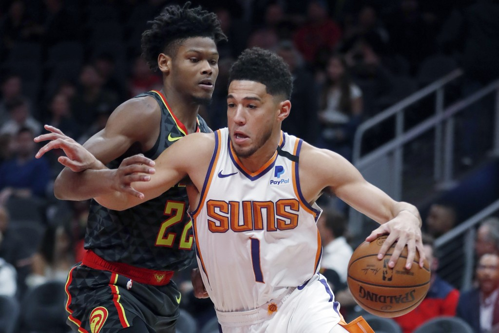Phoenix Suns guard Devin Booker (1) drives against Atlanta Hawks forward Cam Reddish (22) in the first half of an NBA basketball game Tuesday, Jan. 14...