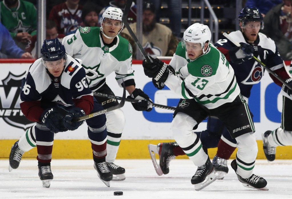 Colorado Avalanche right wing Mikko Rantanen, left, and Dallas Stars center Mattias Janmark, right, pursue the puck as defenseman Andrej Sekera trails...