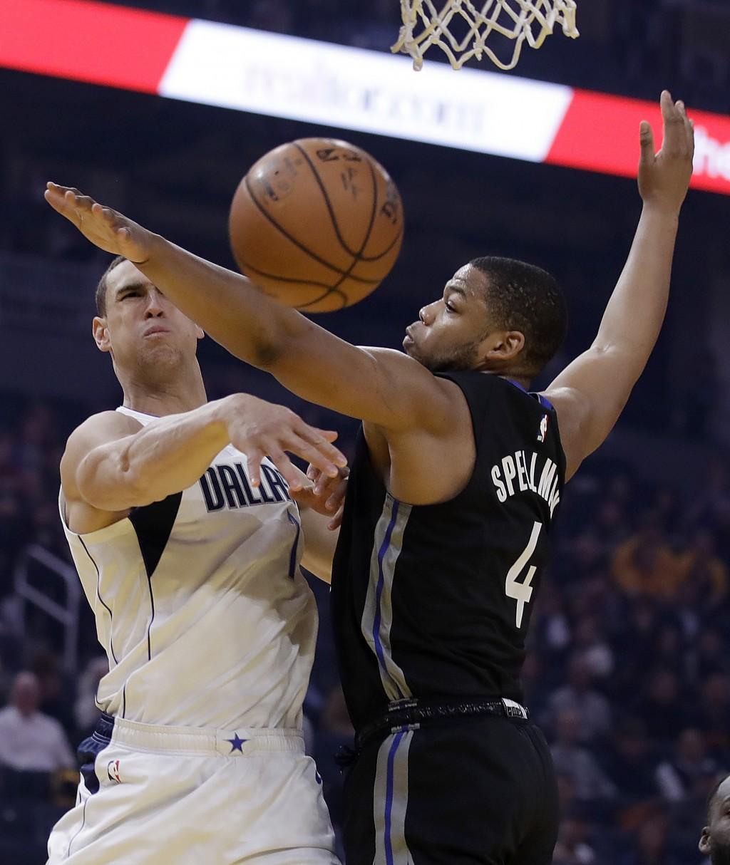Dallas Mavericks' Dwight Powell, left, passes the ball away from Golden State Warriors' Omari Spellman (4) during the first half of an NBA basketball ...