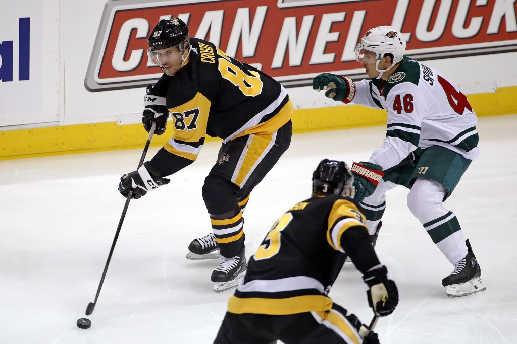 Pittsburgh Penguins' Sidney Crosby (87) looks to pass the puck as Minnesota Wild's Jared Spurgeon (46) defends during the first period of an NHL hocke...