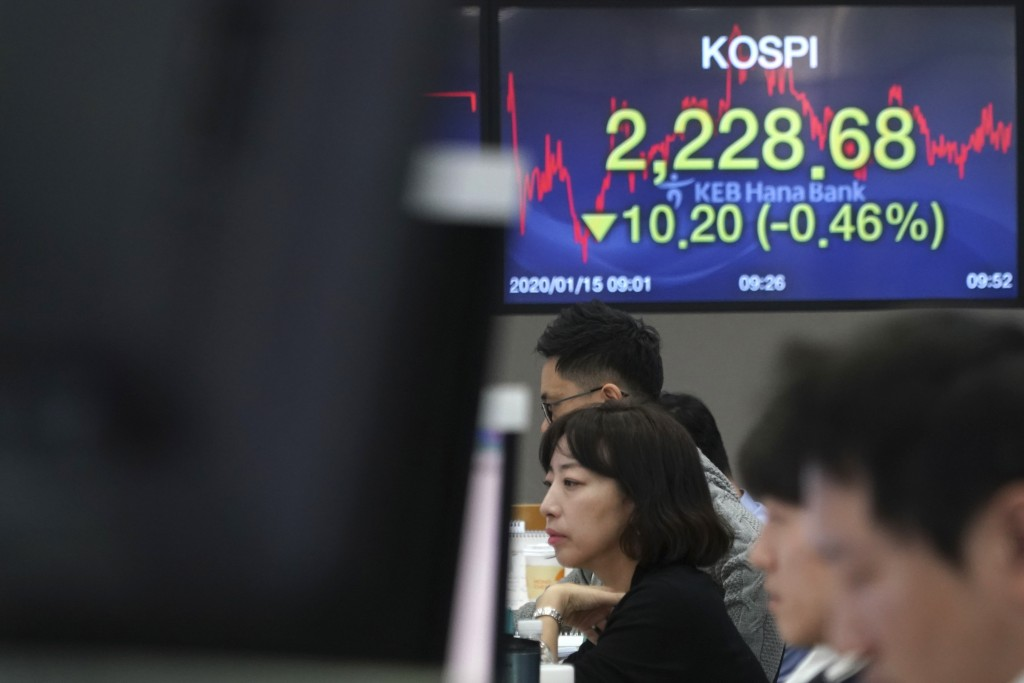 Currency traders watch computer monitors near the screens showing the Korea Composite Stock Price Index (KOSPI), right, and the foreign exchange rates...
