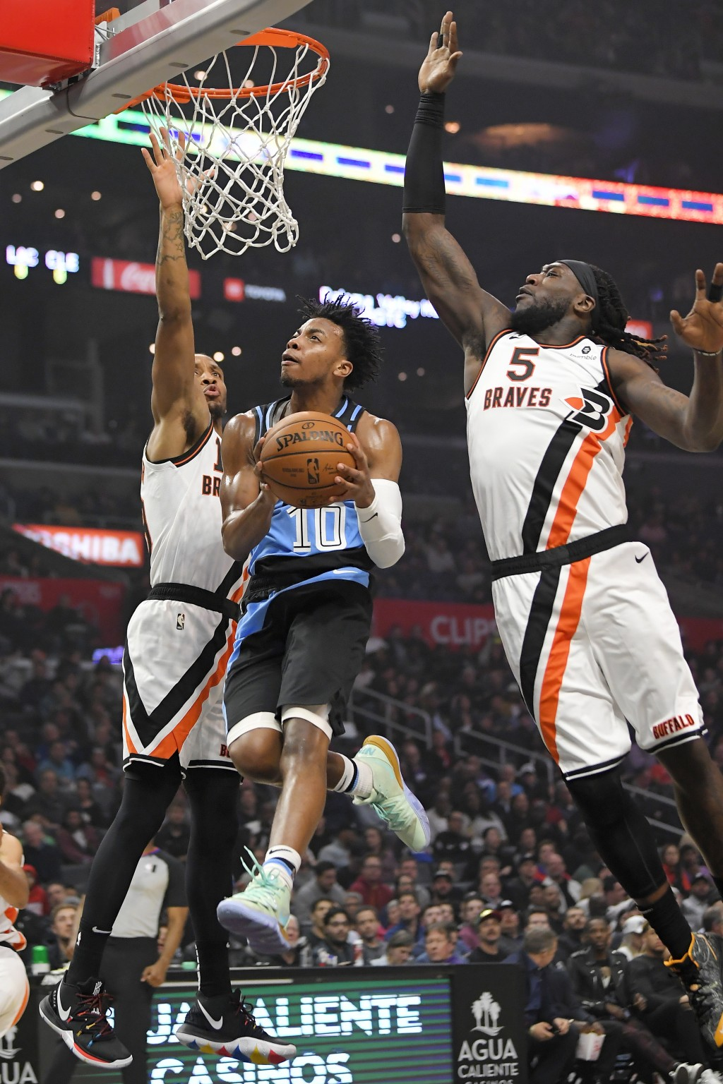Cleveland Cavaliers guard Darius Garland, center, goes up for a shot as Los Angeles Clippers guard Rodney McGruder, left, and forward Montrezl Harrell...