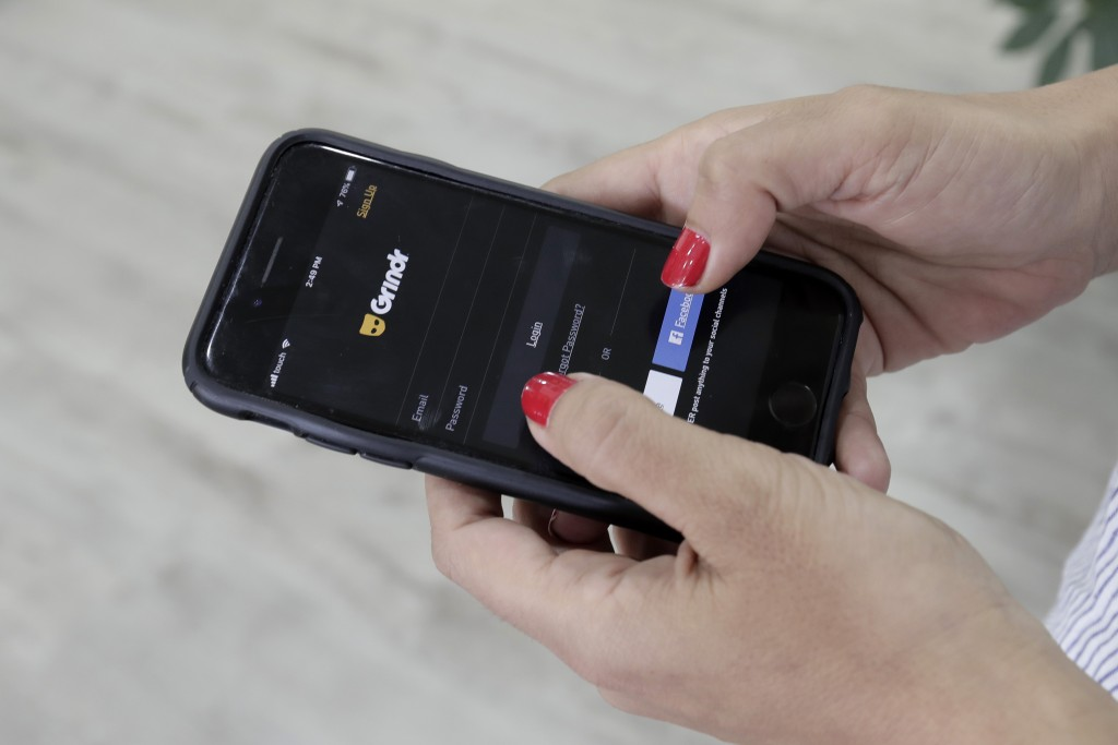 FILE - In this Wednesday, May 29, 2019 file photo, a woman checks the Grindr app on her mobile phone in Beirut, Lebanon. Dating apps including Grindr,...