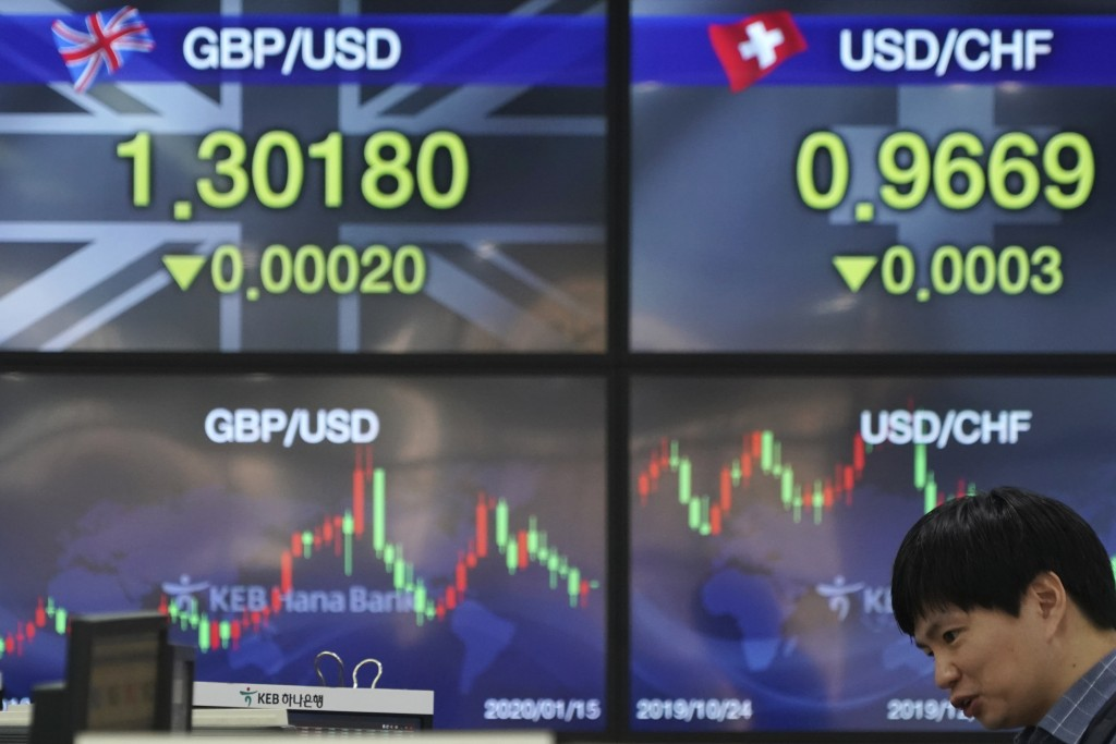 A currency trader talks near the screens showing the foreign exchange rates at the foreign exchange dealing room in Seoul, South Korea, Wednesday, Jan...