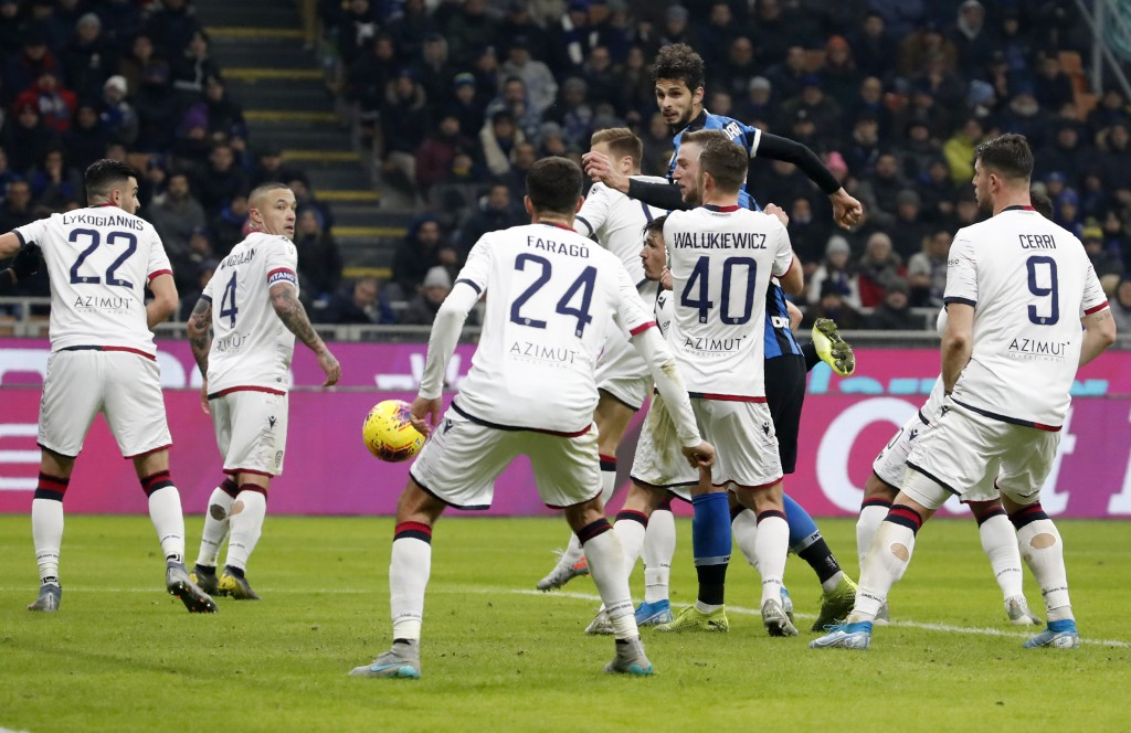Inter Milan's Andrea Ranocchia, top, scores his side's fourth goal during an Italian Cup soccer match between Inter Milan and Cagliari at the San Siro...