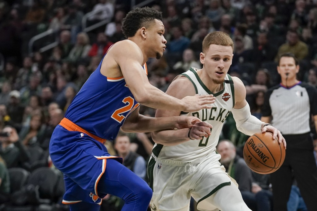 Milwaukee Bucks' Donte DiVincenzo drives past New York Knicks' Kevin Knox II during the second half of an NBA basketball game Tuesday, Jan. 14, 2020, ...