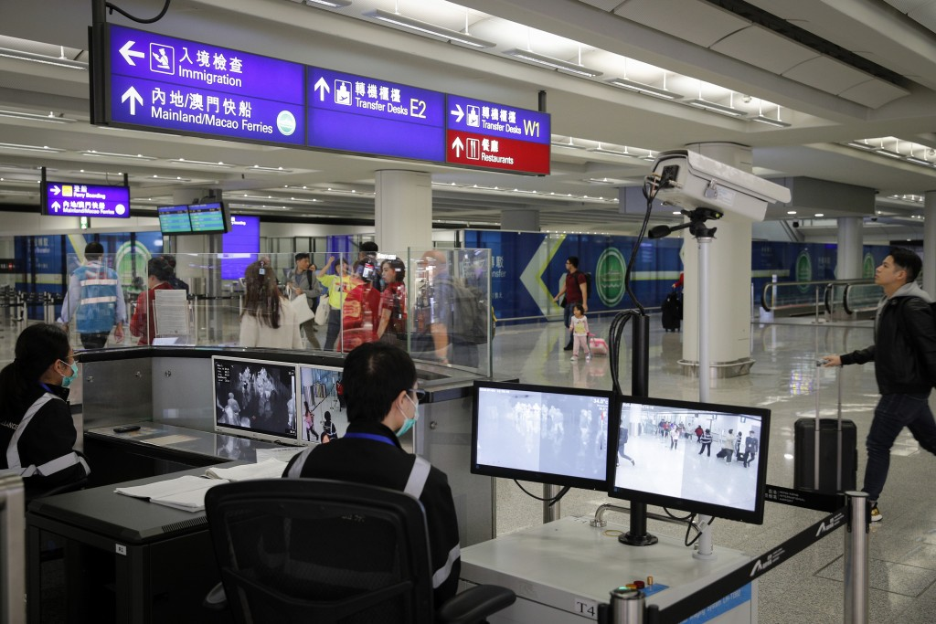 FILE - In this Jan. 4, 2020, file photo, health surveillance officer use temperature scanner to monitor passengers arriving at the Hong Kong Internati...