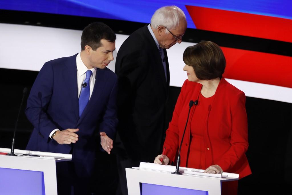 Democratic presidential candidates former South Bend Mayor Pete Buttigieg, left, and Sen. Amy Klobuchar, D-Minn., talk while Sen. Bernie Sanders, I-Vt...