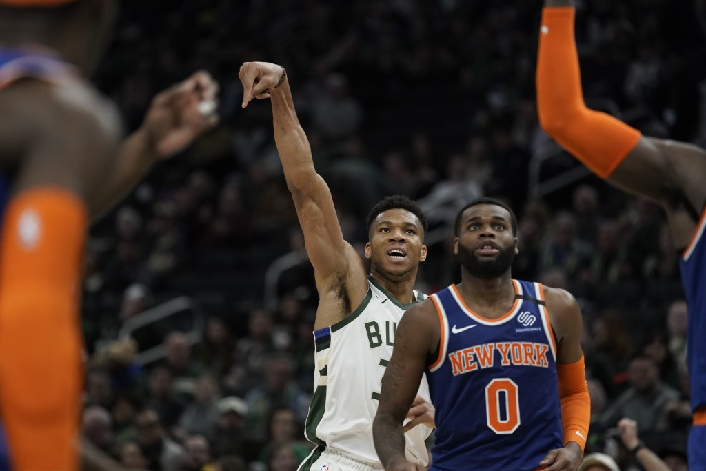 Milwaukee Bucks' Giannis Antetokounmpo shoots a three-point basket during the second half of an NBA basketball game against the New York Knicks Tuesda...