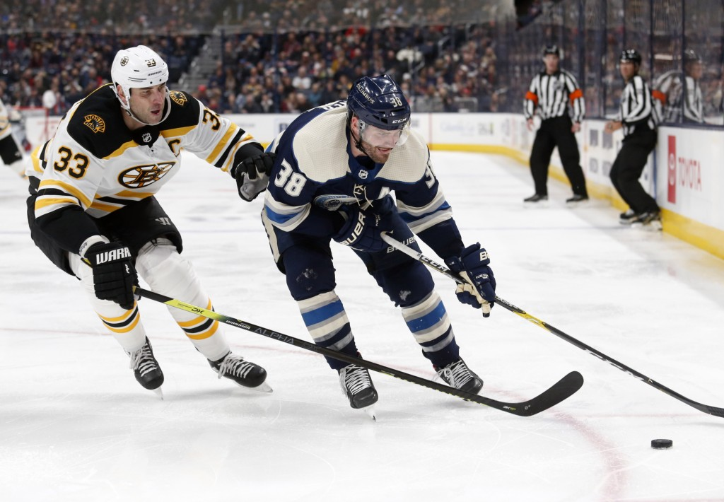 Columbus Blue Jackets forward Boone Jenner, right, chases the puck in front of Boston Bruins defenseman Zdeno Chara, of Slovakia, during the second pe...