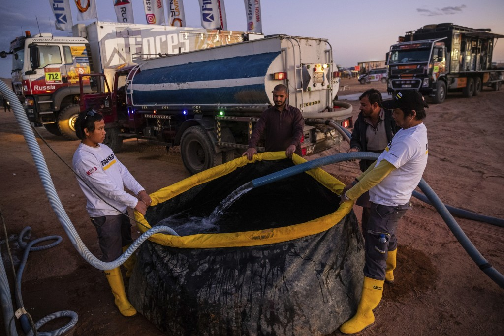 In this Thursday, Jan. 9, 2020 photo, Karcher staffers fill a tank with water to be used for cleaning vehicles at the bivouac of the Dakar Rally in Ha...