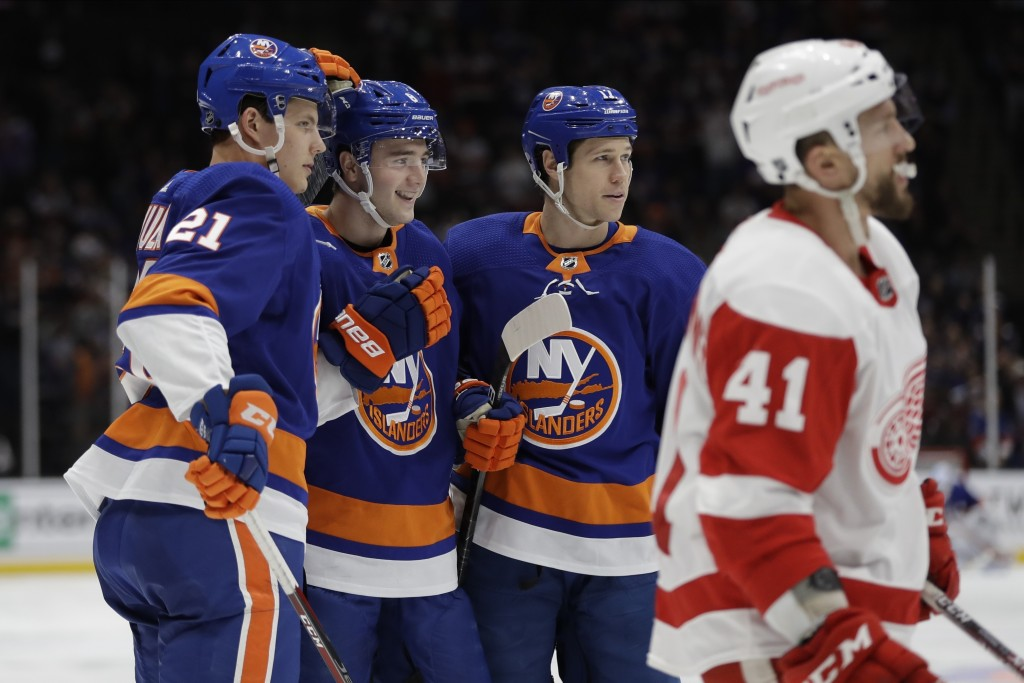New York Islanders' Otto Koivula (21) and Matt Martin (17) celebrate a goal by Noah Dobson during the second period of an NHL hockey game as Detroit R...