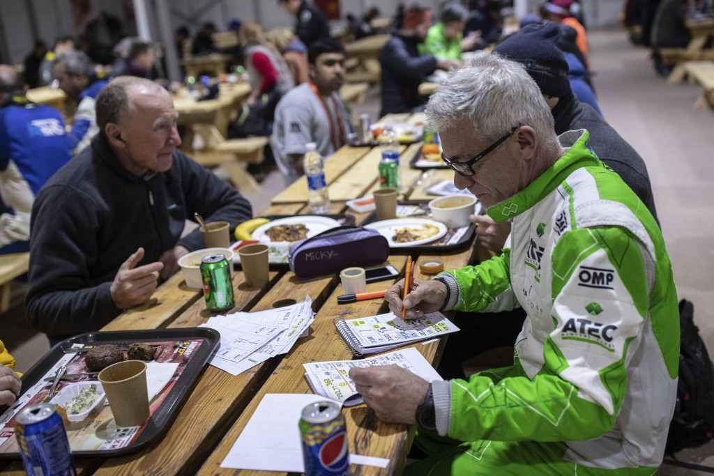 In this Sunday, Jan. 12, 2020 photo, co-driver Maurizio Dominella of Italy, checks the road book for the next stage at the restaurant of the Dakar Ral...