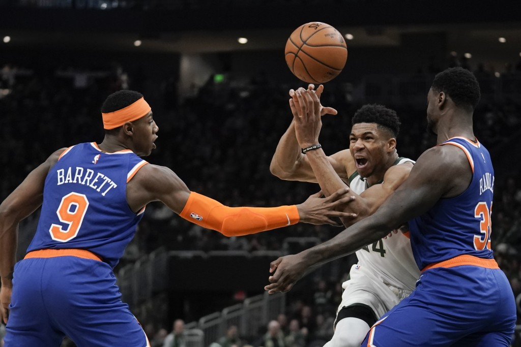 Milwaukee Bucks' Giannis Antetokounmpo is fouled driving between New York Knicks' Julius Randle and RJ Barrett during the second half of an NBA basket...