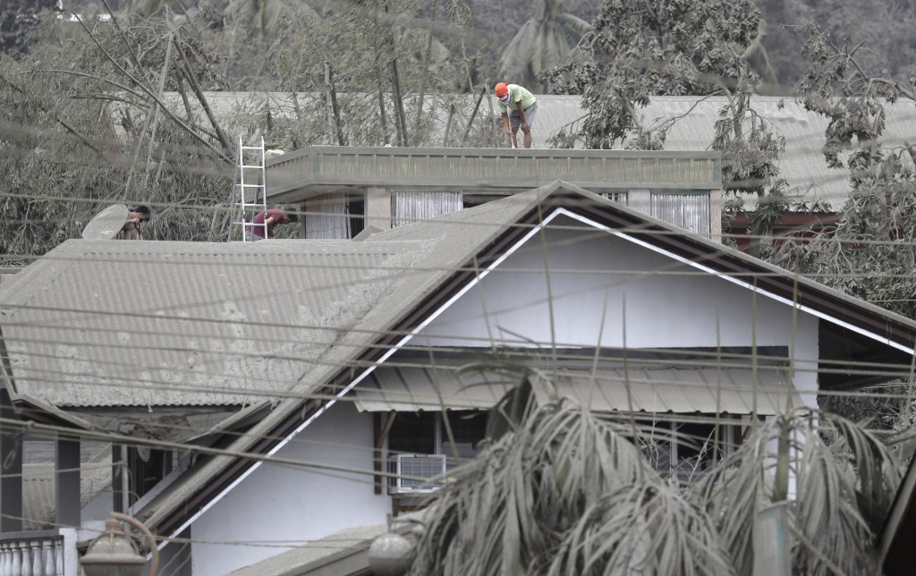 A man sweeps out volcanic ash from the roof of their homes near Taal volcano as residents evacuated to safer grounds in Talisay, Batangas province, so...