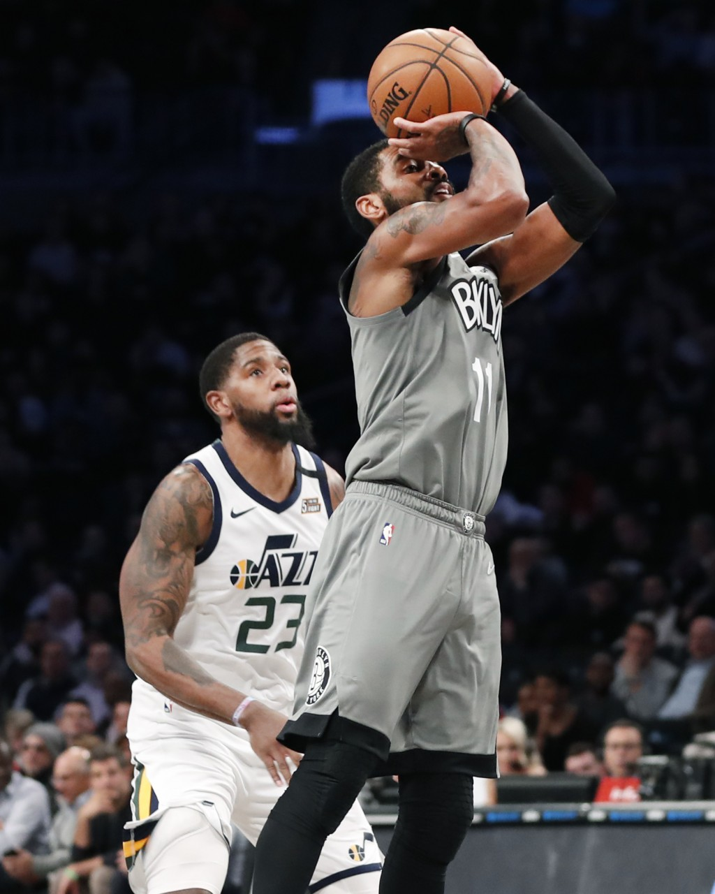 Brooklyn Nets guard Kyrie Irving (11) shoots in front of Utah Jazz forward Royce O'Neale during the second quarter of an NBA basketball game Tuesday, ...