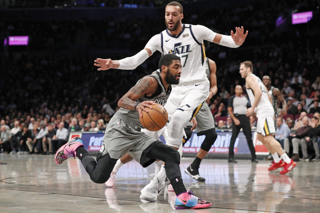 Brooklyn Nets guard Kyrie Irving (11) drives around Utah Jazz center Rudy Gobert (27) during the first quarter of an NBA basketball game Tuesday, Jan....