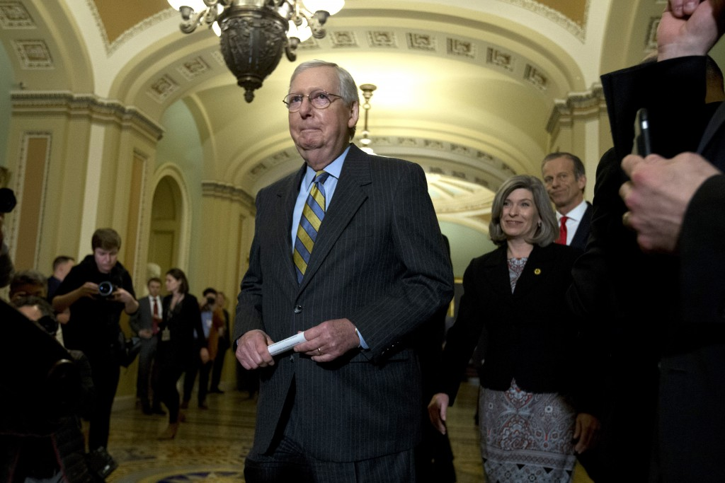 Senate Majority Leader Mitch McConnell, R-Ky., walks to talk with reporters outside of the Senate chamber, on Capitol Hill in Washington, Tuesday, Jan...