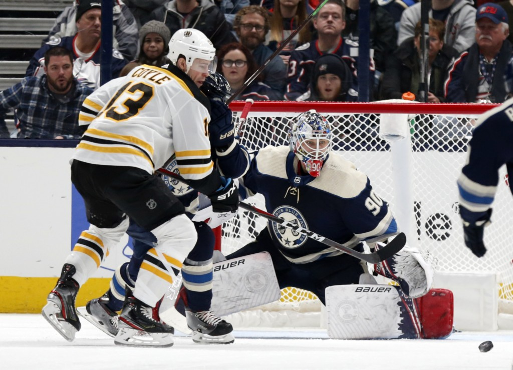 Columbus Blue Jackets goalie Elvis Merzlikins, right, of Latvia, stops a shot from Boston Bruins forward Charlie Coyle, left, during the second period...