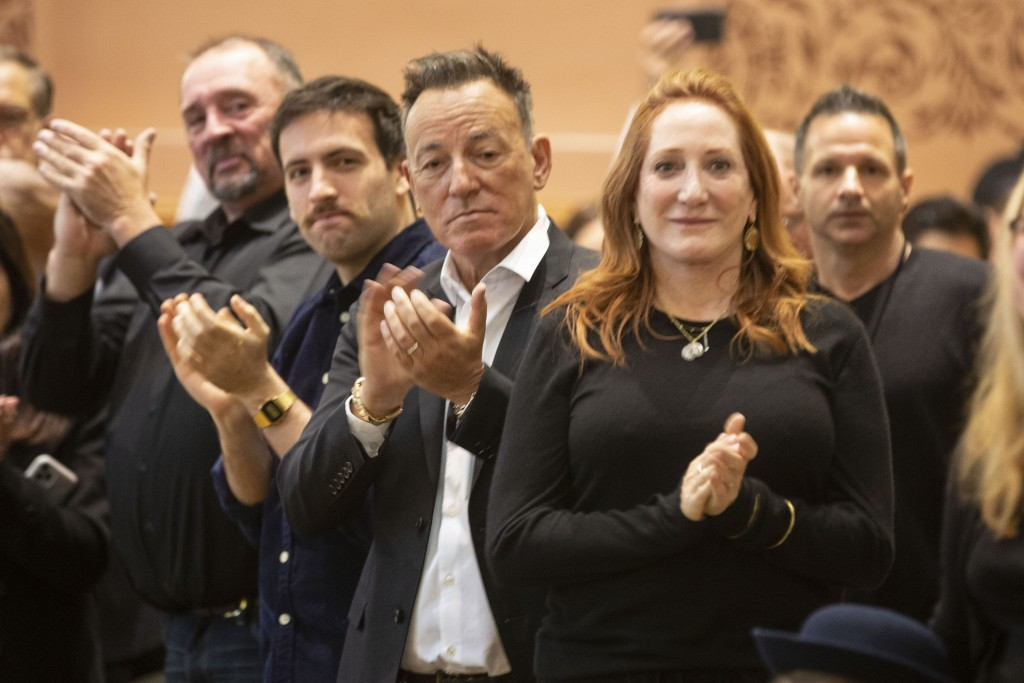 In this photo provided by the Jersey City Mayor's Office, Bruce Springsteen, center, and Patti Scialfa, right, applaud as their son Sam Springsteen is...