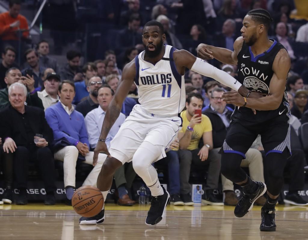 Dallas Mavericks' Tim Hardaway Jr., left, drives the ball against Golden State Warriors' Glenn Robinson III during the first half of an NBA basketball...