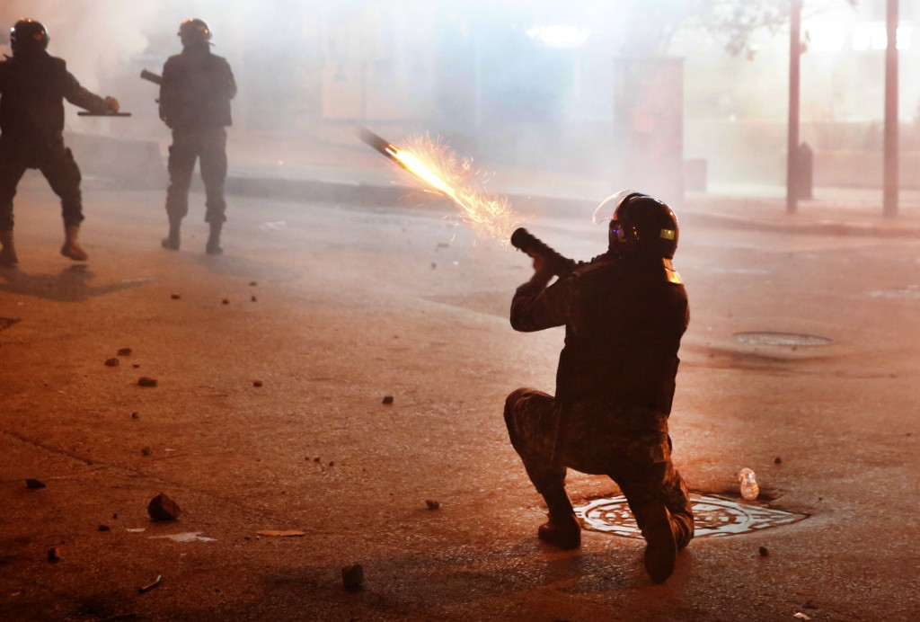 A riot policeman fires tear gas against the anti-government protesters, during ongoing protests against the Lebanese central bank's governor and again...