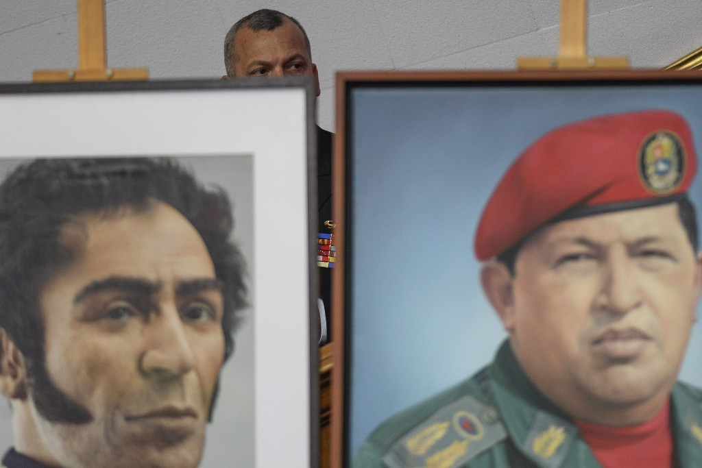 A member of the Venezuelan military sits behind images of late President Hugo Chavez, right, and independence hero Simon Bolivar during the annual add...