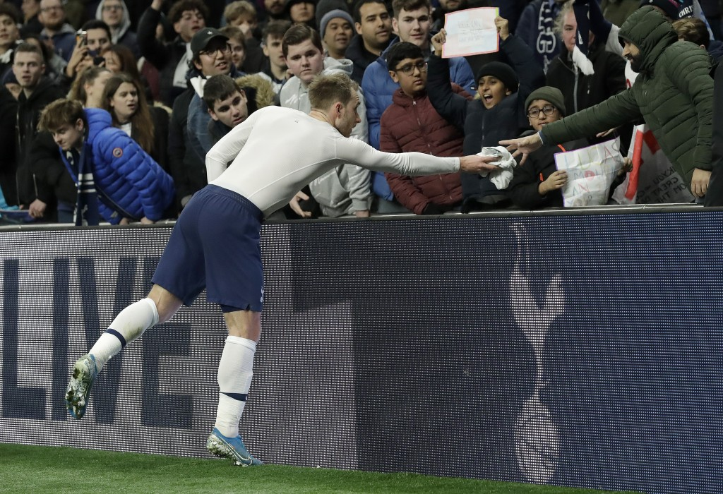 Tottenham's Christian Eriksen hands his shirt to a supporter after the English FA Cup third round replay soccer match between Tottenham Hotspur and Mi...