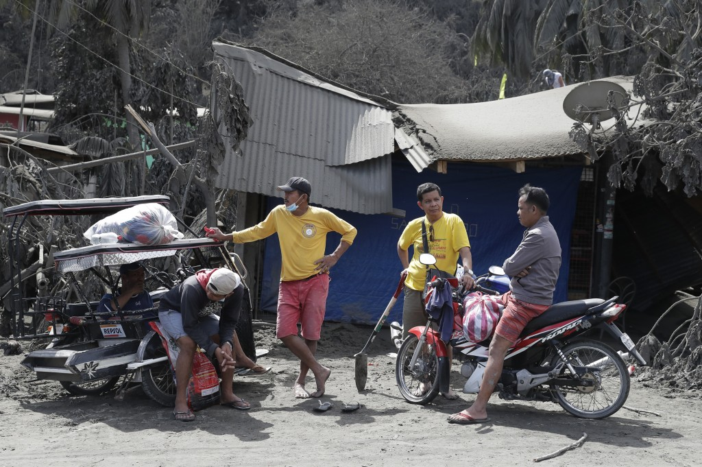 In this Jan. 14, 2020, photo, residents chat beside a damaged structure in Laurel, Batangas province, southern Philippines, as Taal volcano continues ...