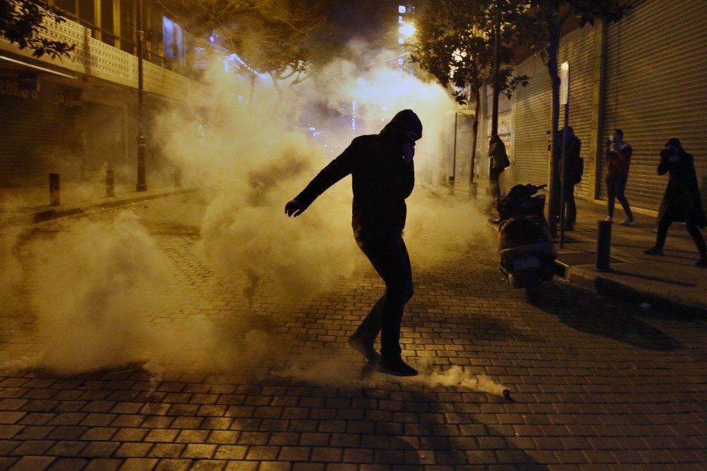 An anti-government protester kicks a tear gas canister that was fired towards them by riot police, during ongoing protests against the Lebanese centra...