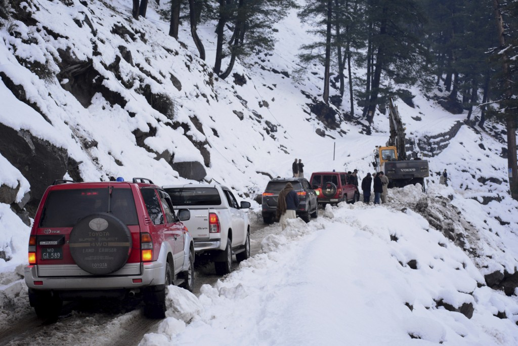 Vehicles are stranded on a snow-covered road as workers with heavy machinery try to make it passable, in Keran, a small town in Neelum Valley, Pakista...