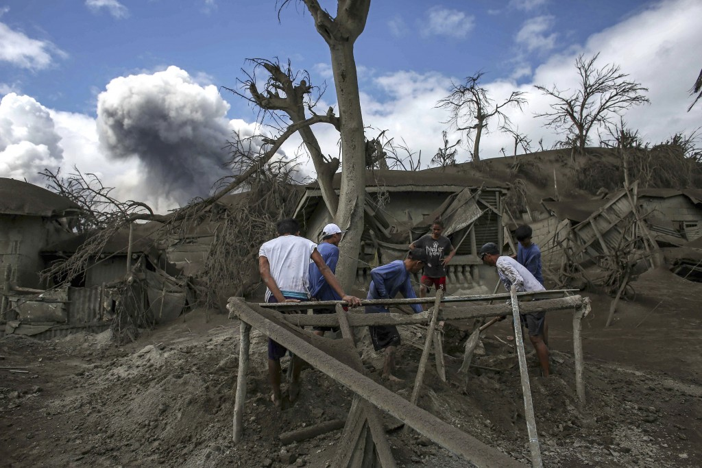 In this Jan. 14, 2020, photo, men recover items on Taal volcano island as it continues to spew ash in Talisay, Batangas province, southern Philippines...