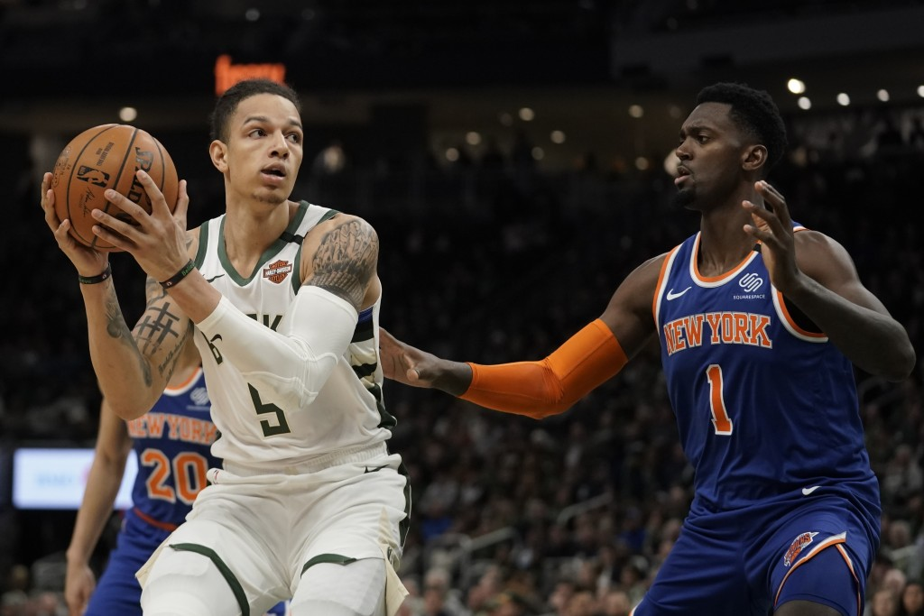 Milwaukee Bucks' D.J. Wilson tries to get past New York Knicks' Bobby Portis during the second half of an NBA basketball game Tuesday, Jan. 14, 2020, ...