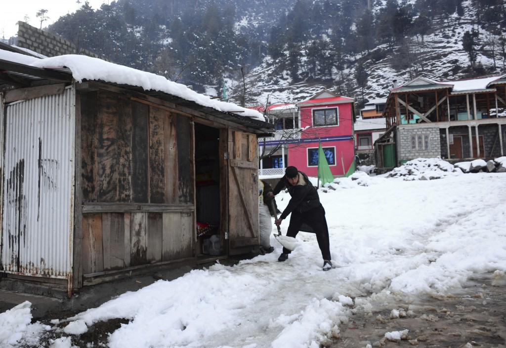 A man removes snow from outside his house after heavy snowfall, in Keran, a small town in Neelum Valley, Pakistan-administered Kashmir, Tuesday, Jan. ...