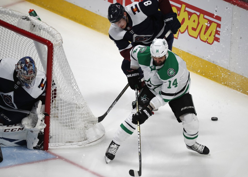 Dallas Stars left wing Jamie Benn, front right, loses control of the puck as Colorado Avalanche defenseman Cale Makar, back right, and goaltender Phil...