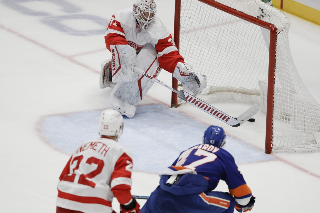Detroit Red Wings goaltender Calvin Pickard, above, reaches for the puck shot by New York Islanders' Leo Komarov, right, for a goal during the third p...